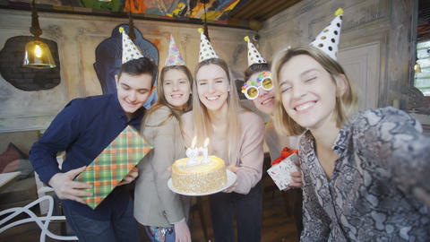 Happy attractive friends in birthday party hats are taking selfie. Look at the Live Action