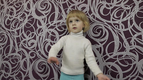 Little happy child dancing on sofa and listening music at home. Slow motion Footage