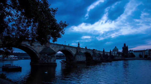 Charles Bridge of Prague at night. Gradually the night comes. In the sky dense Live Action