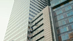 Three Window Washers Men Cleaning Glass Windows on Modern Office Building Facade Footage