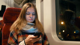Young Lady is Using Phone in Public Transport Train at Night Sitting near Window Footage