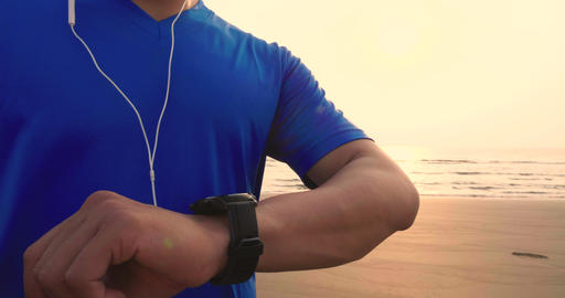 [alt video] young Man running on beach and checking Heart Rate...