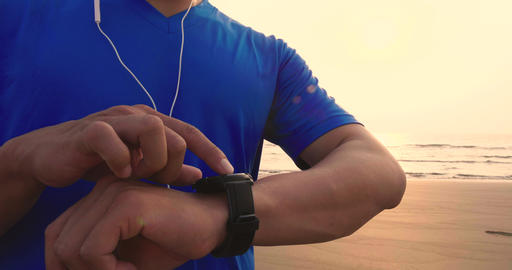 young Man running on beach and checking Heart Rate Monitor On watch Archivo