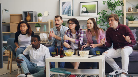 Multiracial group of young people cheering sports team watching TV at home Live Action