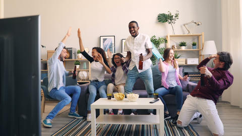 Sporty youth watching sports game on TV laughing doing high-five holding beer Live Action