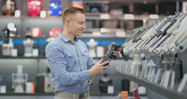 A man chooses a blender in the appliances store kitchen appliances in his hands Footage