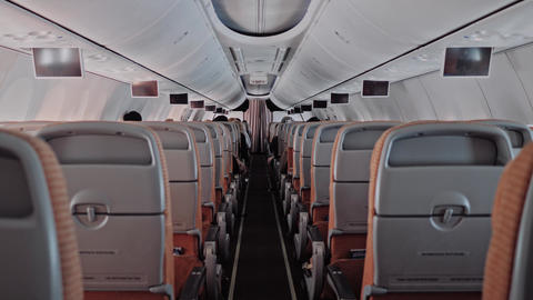 Backside view modern large airliner passenger cabin people rest and watch tv GIF