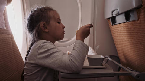 The child is flying on an airplane to rest. A girl sitting near the window and GIF