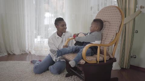 Joyful cute african american woman playing with her small cute and funny son Footage