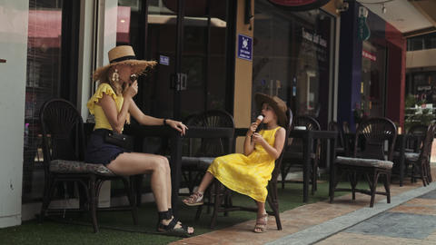 Mother and daughter eating icecream at the street cafe in... Stock Video Footage