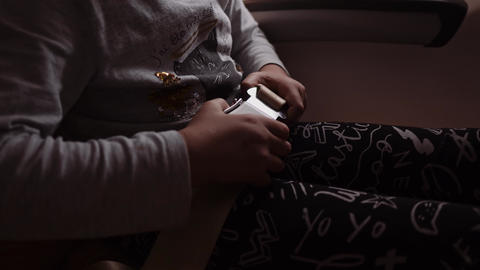 close up shot of a girl's hands, who is fasten a seatbelt in an airplane chair Footage