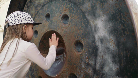 Little girl rub the round metal gong to make a sound Footage