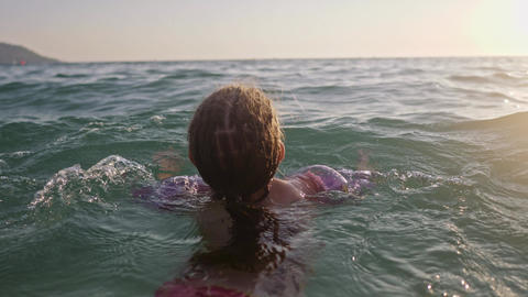 Little young girl learning to swim in the sea Footage