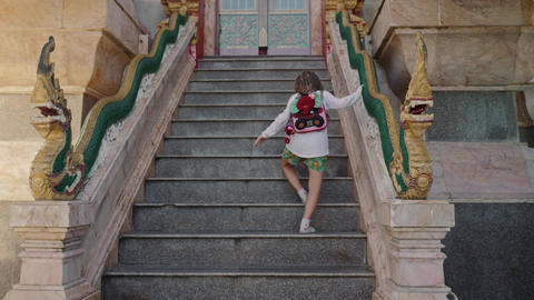 Little tourist girl walk upstairs to buddha temple GIF