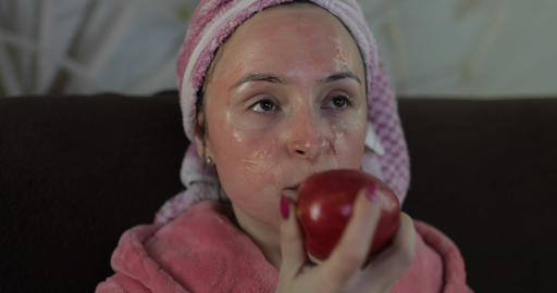 Woman watching a late night movie at TV, eating an apple.... Stock Video Footage