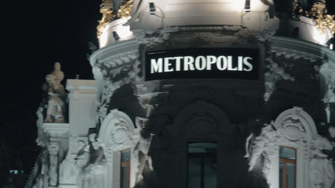 Night view of Metropolis Building, facade details. Landmark of Madrid, Spain Live Action