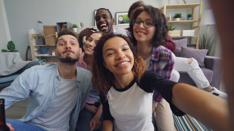 Happy friends taking selfie at home holding camera having fun looking at camera Live Action