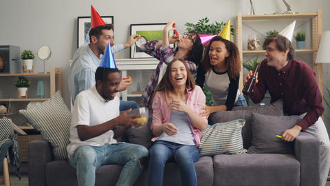Laughing friends in party hat congratulating girl on birthday feeding her crisps Footage