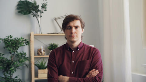 Slow motion portraif of attractive person standing at home with arms crossed Footage