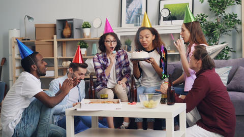 Slow motion of youth celebrating birthday with cake, confetti and party whistles Footage