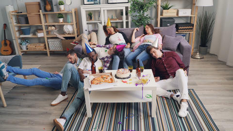Tired men and women sleeping on couch and floor after enjoyable party in flat Live Action
