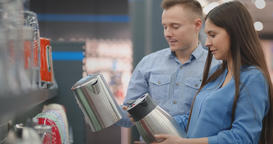 A man and woman hold in their hands an electric kettle in a store choosing Footage