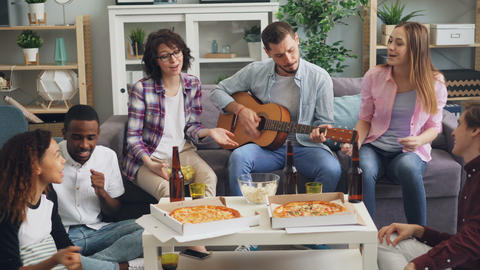 Men and women friends playing the guitar and singing together at party in house Archivo