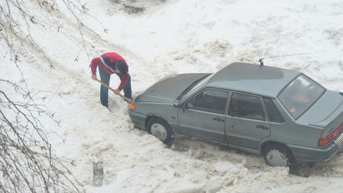 Man digs a shovel of snow from a car stuck in the snow Footage