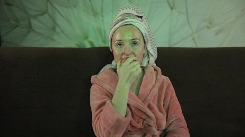 Woman watching a late night movie at TV, eating an apple. Bathrobe, facial mask Footage