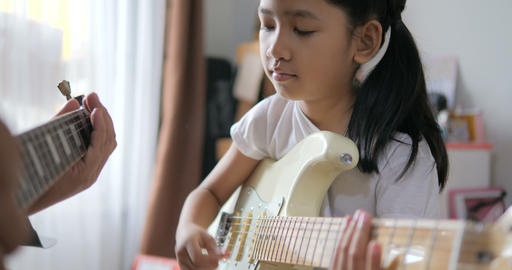 Asian little girl learning to play basic guitar by using electric guitar for beginner music Footage