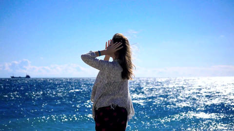 Young woman standing near the sea in windy weather Footage