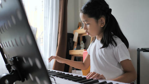 Asian little girl learning to play basic piano by using electric synthesizer keyboard for beginner Footage