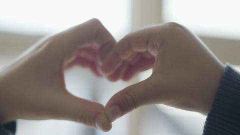 Heart shaped by child hands close up. Cute children depict heart shape with Footage
