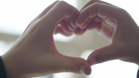 Heart shaped by child hands. Cute children depict heart shape with their fingers Footage