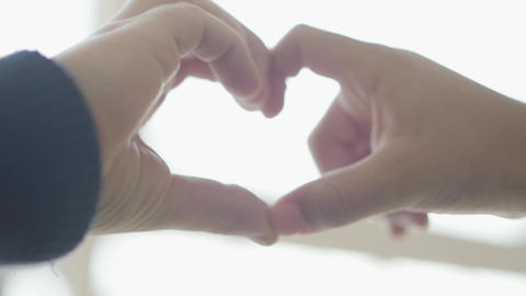 Cute children depict heart shape with their fingers close up. Heart shaped by Footage