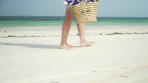 Young woman walks barefoot on beach along ocean Live Action