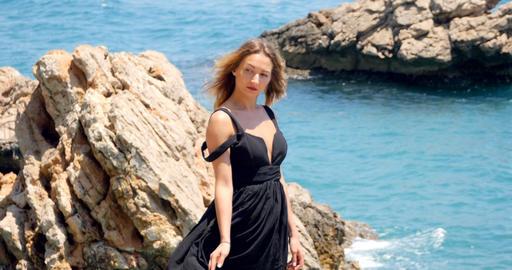Young pretty woman in black cutout elegant dress sitting near the sea Footage
