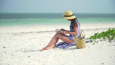 Young caucasian woman reading book on the beach Footage
