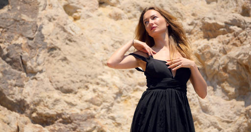 Beautiful woman with deep cutout elegant black dress on the rocks Footage