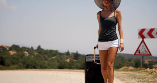 young woman in white shorts goes alone along the road with luggage Footage
