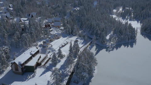 Aerial - Holiday chalets and hotel near the frozen lake amongst the snow-capped Footage