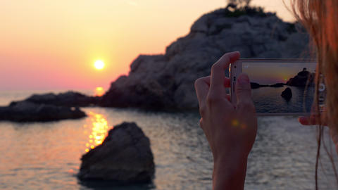 Young woman taking photo of the sunset with her phone on the beach Footage
