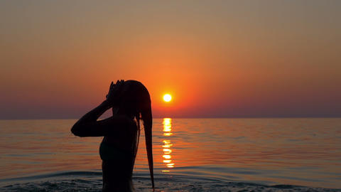 Slow motion - Woman splashes water with hair and looks at the sunset Footage