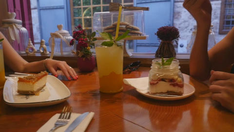 Young women drinking lemonade and eating cakes at the cafe Footage