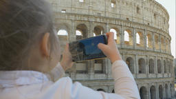 Cute little girl with parents takes photos of city sights Footage