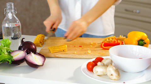 Close-up of a young attractive woman cutting raw corn on a cutting Board Footage