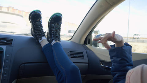 Legs young girl lying on dashboard car moving to music beat on window background Live Action