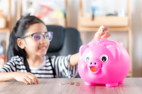 Asian little girl in putting coin in to piggy bank shallow depth フォト