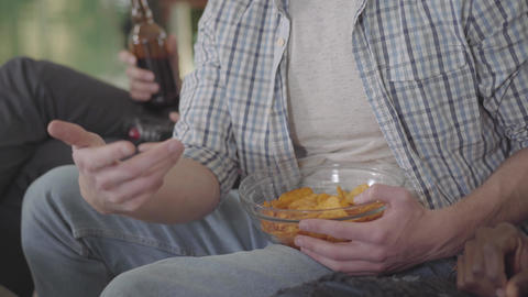 Friends have a rest drinking beer and eating chips sitting on the couch indoors Footage