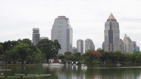 Urban cityscape: green trees and large lake in front of skyscrapers in downtown Footage